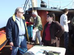 In gesprek aan boord van het schip van Rijkswaterstaat, op weg naar het REM-eiland.